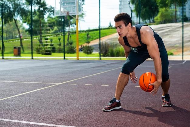 Homem jogando basquete na quadra do parque