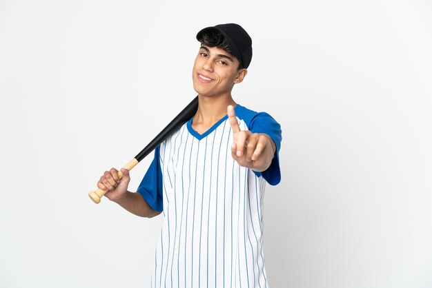 Homem jogando beisebol sobre fundo branco isolado, mostrando e levantando um dedo