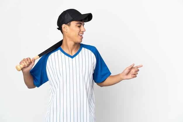 Homem jogando beisebol sobre um fundo branco isolado apontando o dedo para o lado e apresentando um produto