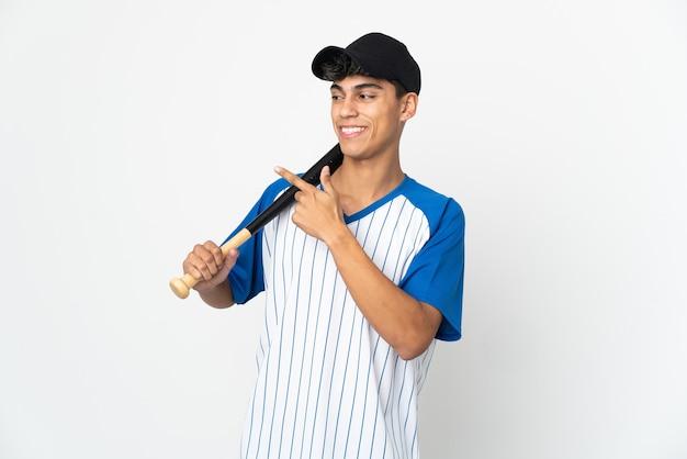 Homem jogando beisebol sobre um fundo branco isolado apontando para o lado para apresentar um produto