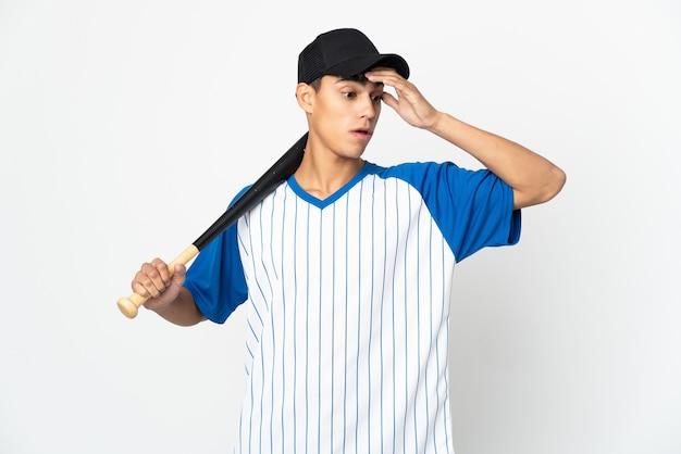 Homem jogando beisebol sobre um fundo branco isolado fazendo gesto de surpresa enquanto olha para o lado