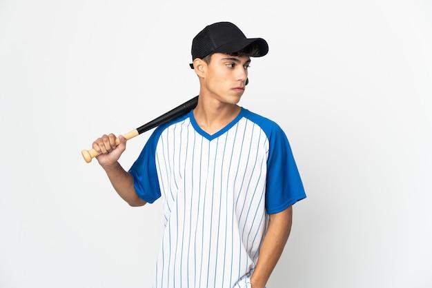 Homem jogando beisebol sobre um fundo branco isolado, olhando para o lado