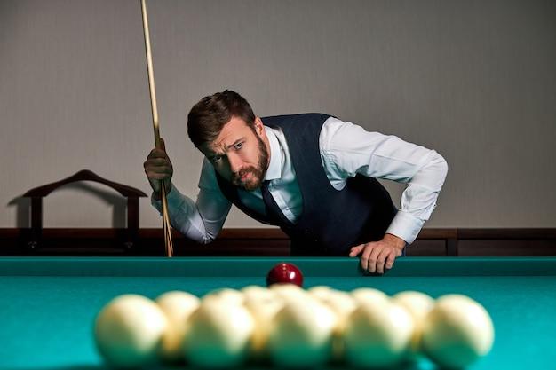 Homem jogando bilhar ou sinuca com concentração e cara séria olhando para as bolas na mesa, conceito de jogo de esporte