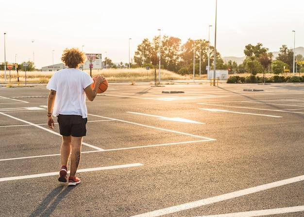 Homem jogando bola de basquete no tribunal durante o dia de sol