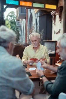 Homem jogando cartas. homem barbudo de cabelos grisalhos jogando cartas com os amigos enquanto está sentado do lado de fora do bar