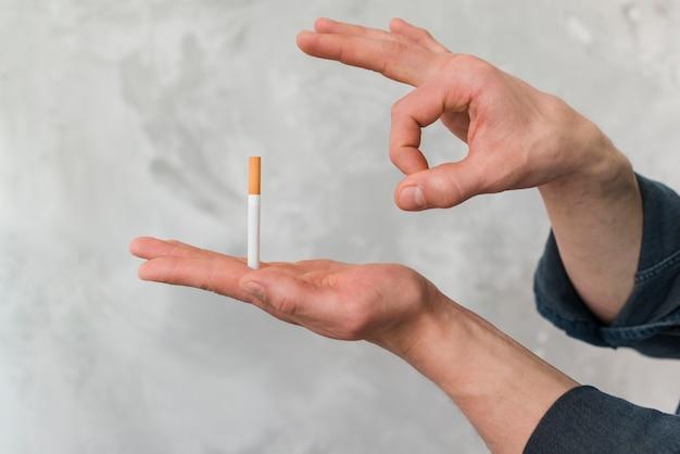 Homem, jogando cigarro, através, dedo, contra, parede