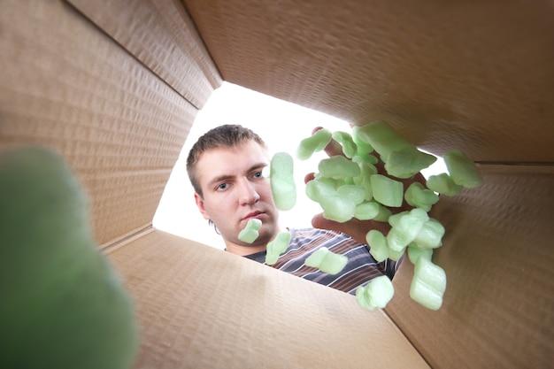 Homem jogando espuma de plástico em uma caixa de papelão