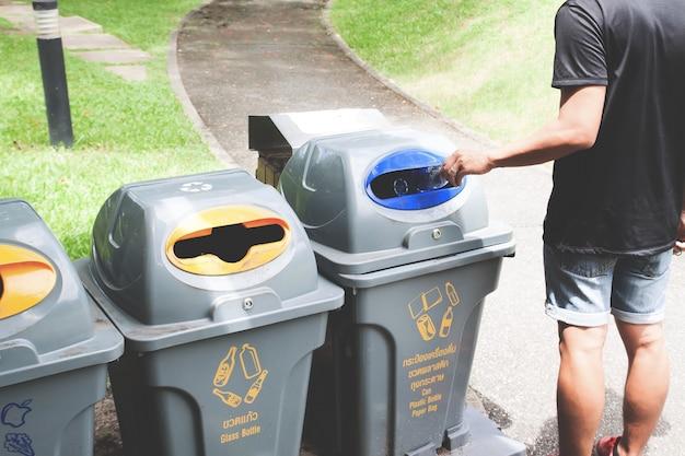 Homem jogando garrafa de plástico na lata de lixo de reciclagem