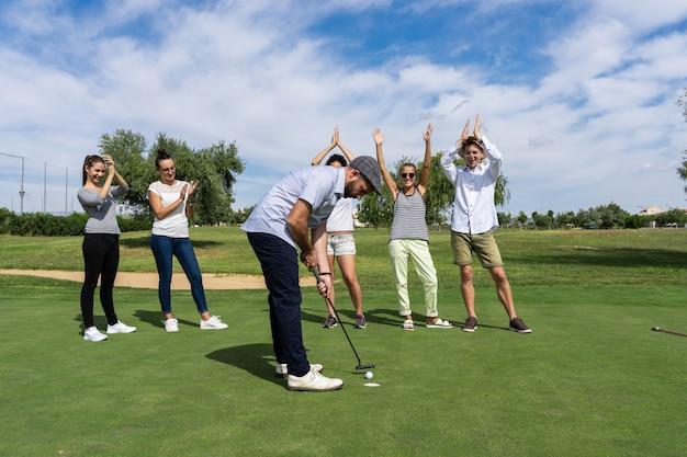 Homem jogando golfe com um taco de golfe na frente de um grupo de pessoas que estão aplaudindo