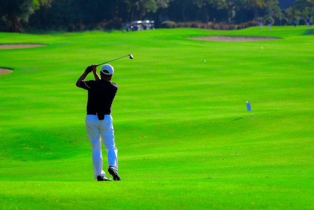 Homem jogando golfe em um campo de golfe, pro golf, colocando a bola no buraco.