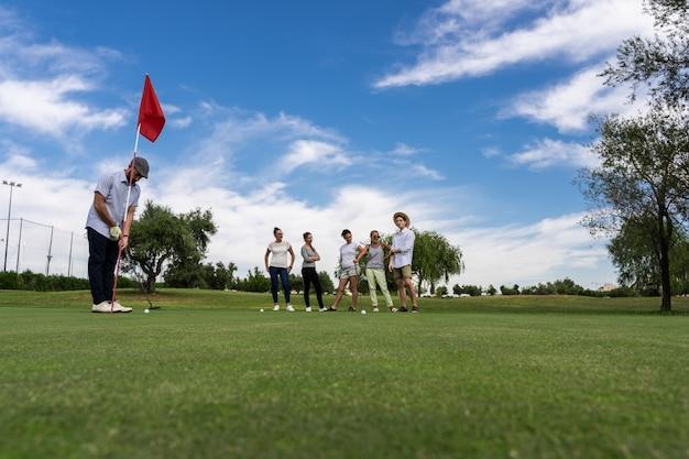 Homem jogando golfe na frente de um buraco e pessoas assistindo em um campo de golfe