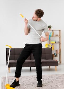 Homem jogando na vassoura durante a limpeza