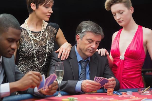 Homem jogando poker com duas mulheres ao lado dele