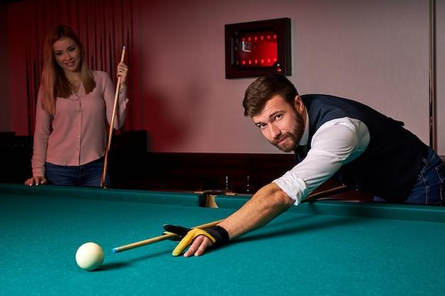 Homem jogando sinuca, forro para bater a bola na mesa de bilhar. passatempo agradável no bar depois do trabalho