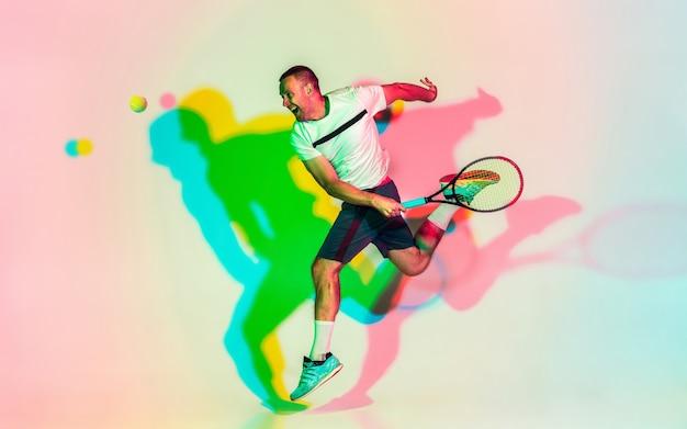 Homem jogando tênis isolado no estúdio com luz de néon da moda