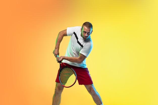 Homem jogando tênis isolado no estúdio sob luz de néon