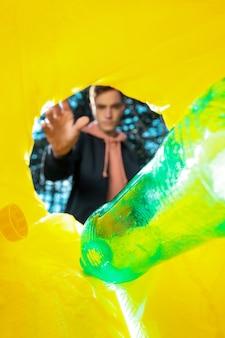 Homem jogando uma garrafa de plástico verde em uma lata de lixo.