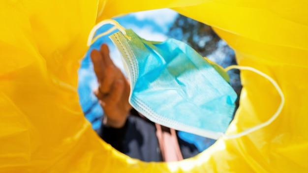Homem jogando uma máscara médica em uma lata de lixo.