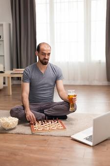 Homem jogando xadrez com amigos de casa