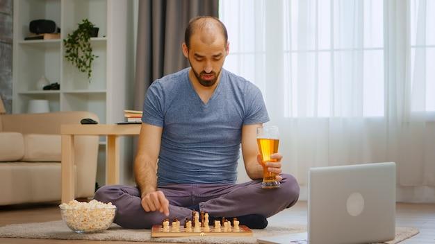 Homem jogando xadrez em videochamada com seus amigos durante a pandemia global.