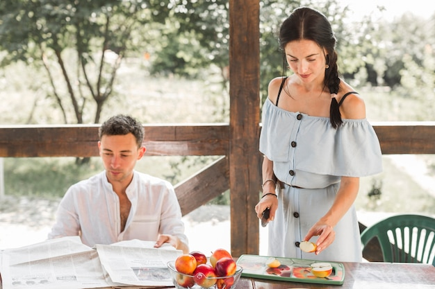 Homem, jornal leitura, com, seu, esposa, corte, frutas