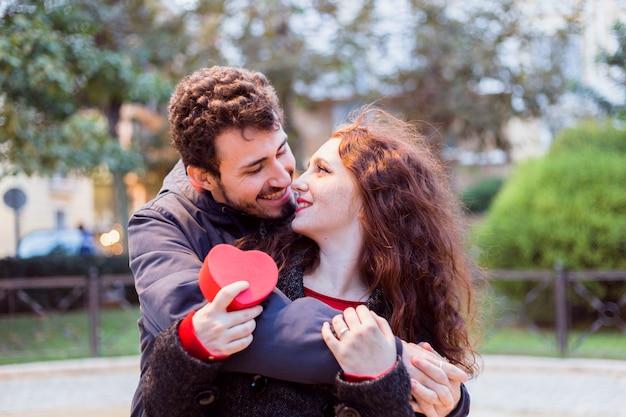 Homem jovem, abraçando, mulher, com, caixa presente, detrás