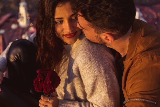 Homem jovem, abraçando, mulher, com, flores vermelhas