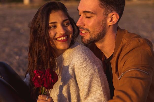 Homem jovem, abraçando, mulher, com, rosas vermelhas