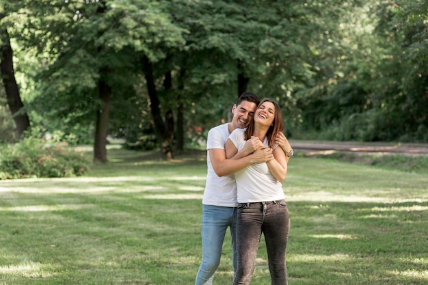 Homem jovem, abraçando, seu, namorada, parque