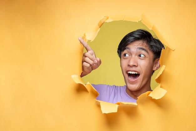 Homem jovem adolescente asiático animado feliz posa através do buraco de papel amarelo rasgado, apontando um espaço de cópia ou papel amarelo em branco, vestindo uma camiseta roxa, anunciando o melhor produto. negócios de publicidade.