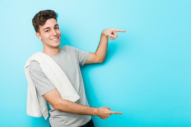 Homem jovem adolescente fitness animado apontando com o dedo indicador fora.