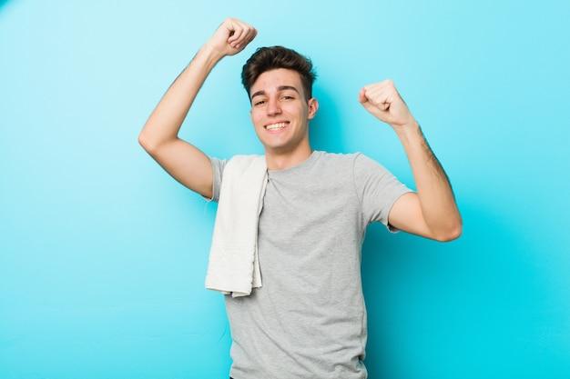 Homem jovem adolescente fitness comemorando um dia especial, saltos e levante os braços com energia.