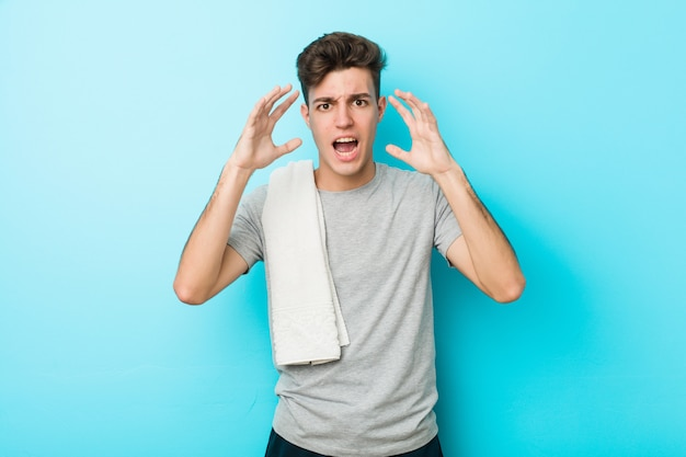 Homem jovem adolescente fitness gritando de raiva.