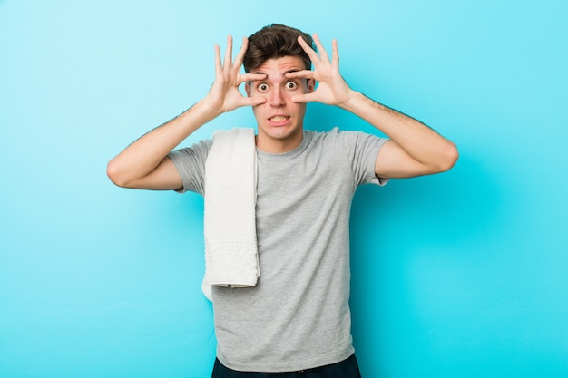Homem jovem adolescente fitness, mantendo os olhos abertos para encontrar uma oportunidade de sucesso