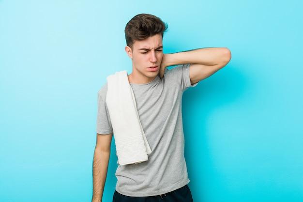 Homem jovem adolescente fitness sofrendo dores no pescoço devido ao estilo de vida sedentário.