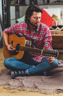 Homem jovem, afinando, violão, sentar chão