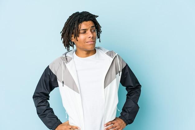 Homem jovem afro-americano do esporte confuso, sente-se em dúvida e inseguro.