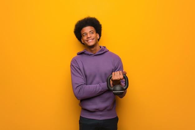 Homem jovem afro-americano fitness segurando um haltere sorrindo confiante e cruzando os braços, olhando para cima