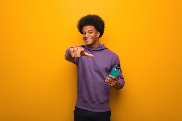 Homem jovem afro-americano fitness segurando uma bebida energética alegre e sorridente apontando para a frente
