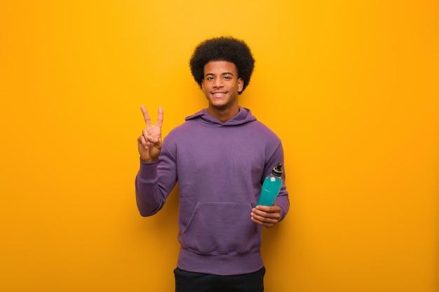 Homem jovem afro-americano fitness segurando uma bebida energética, mostrando o número dois