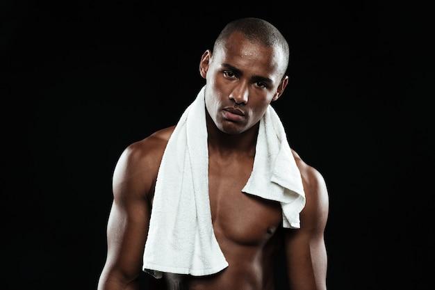 Homem jovem afroamerican esportes com uma toalha branca sobre os ombros, descansando depois de treino,
