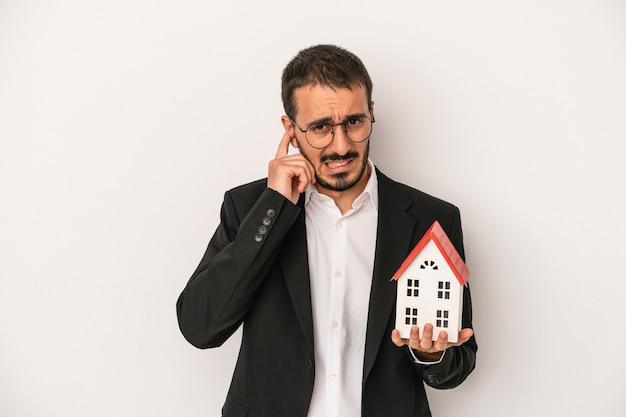 Homem jovem agente imobiliário segurando uma casa modelo isolada no fundo branco, cobrindo as orelhas com as mãos.