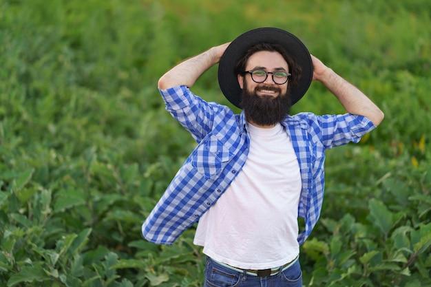 Homem jovem agricultor possing feliz em seu jardim de berinjelas. conceito de agricultura, produtos orgânicos, alimentação limpa, produção ecológica. fechar-se