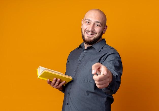 Homem jovem alegre e careca de call center segurando um livro e apontando para a frente, isolado em laranja