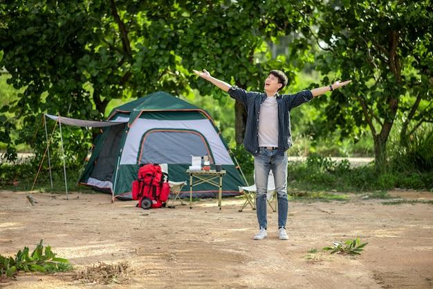 Homem jovem alegre mochileiro de pé e de braços abertos na frente da barraca na floresta com conjunto de café e fazendo moedor de café fresco durante o acampamento nas férias de verão