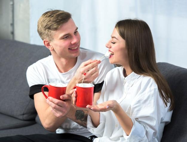 Homem jovem, alimentação, mulher, com, marshmallow, ligado, sofá
