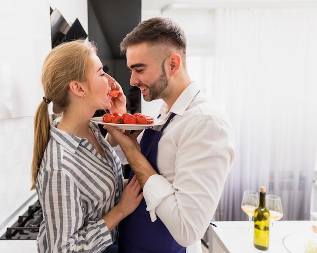 Homem jovem, alimentação, mulher, com, tomates