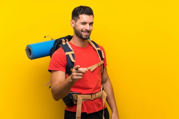 Homem jovem alpinista aponta o dedo para você
