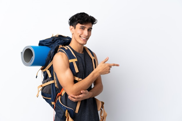 Homem jovem alpinista argentino sobre parede branca isolada, apontando o dedo para o lado