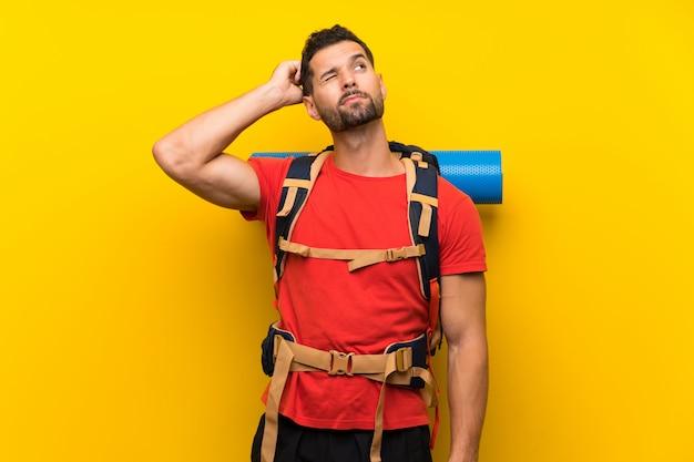 Homem jovem alpinista com dúvidas e com a expressão do rosto confuso